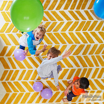 Kids playing with balloons over yellow-and-white rug