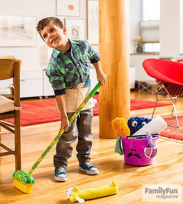 Boy wearing nail apron and holding push broom