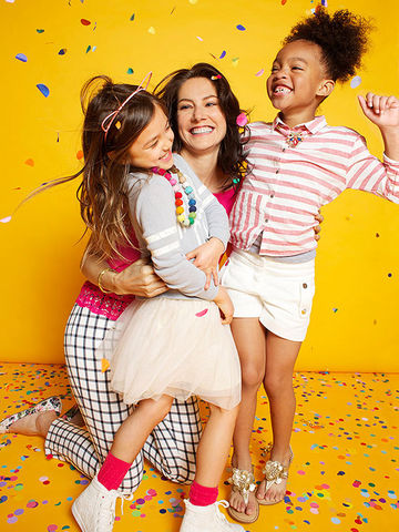 Woman hugging two girls, all on floor covered in confetti