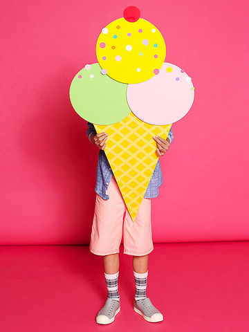 Kid standing behind large paper ice cream cone