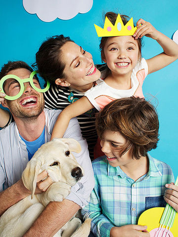 Goofy posing family with dog, man in oversized paper glasses