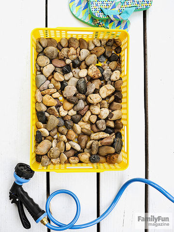 Yellow tray of rocks with flip-flops over it and sprayer hose under it