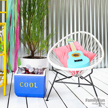 "Blue cooler labeled ""COOL"" next to chair with ukulele in it"