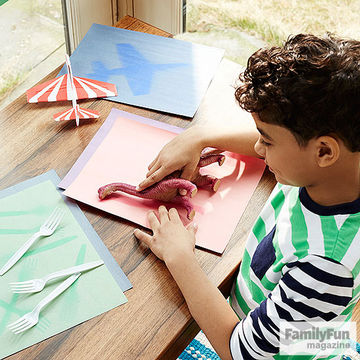 Boy in striped shirt printing dinosaur toy on piece of construction paper