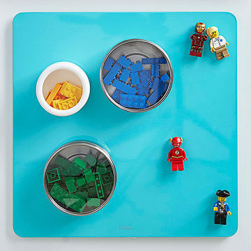 Blue magnet board with circular spice containers and Lego characters attached