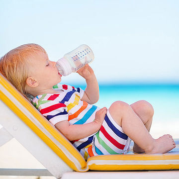baby on beach drinking bottle