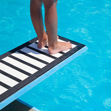 child standing on diving board of pool