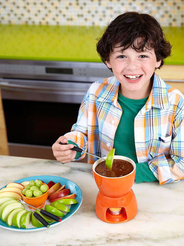 Boy in plaid shirt dipping apple in Caramel Cream Fondue