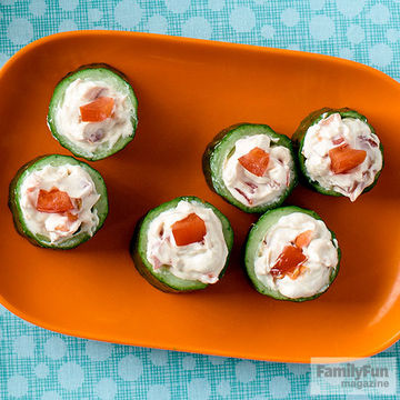 Cucumber cups filled with white filling atop a red-orange plate