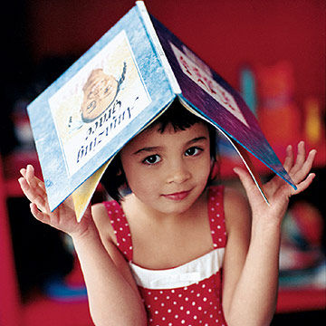 Girl holding book over her head