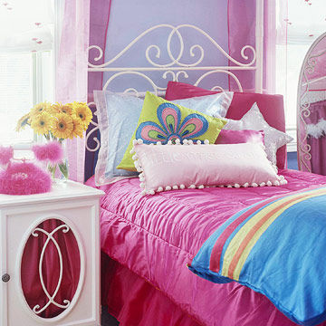 white wrought iron bed with a pink comforter and pillows