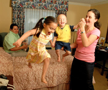 Kids jumping on beds in a family hotel room