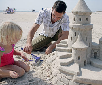 Father and daughter building a sand castle