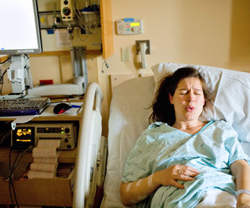 pregant woman breathing in hospital bed