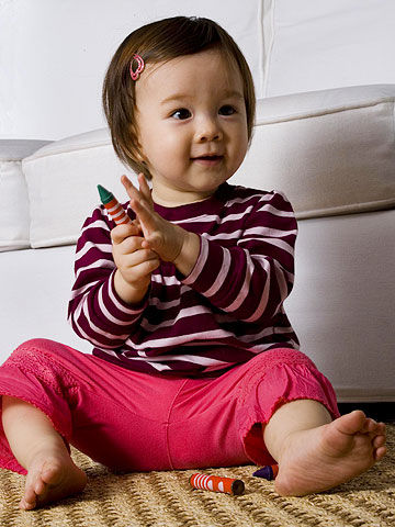 toddler holding crayons