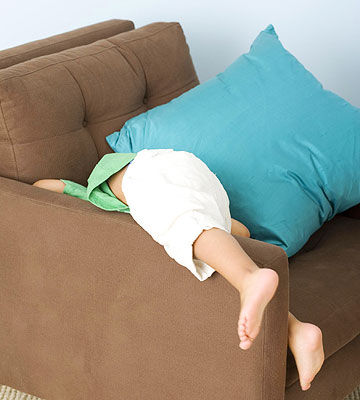 child hiding face in couch