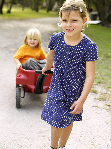 girl pulling brother in red wagon