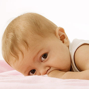 baby lying on tummy with hands in mouth