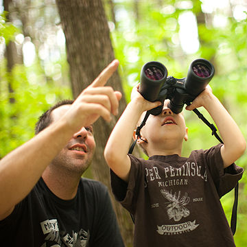 child using binoculars to explore nature