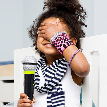 child covering her eyes holding microphone