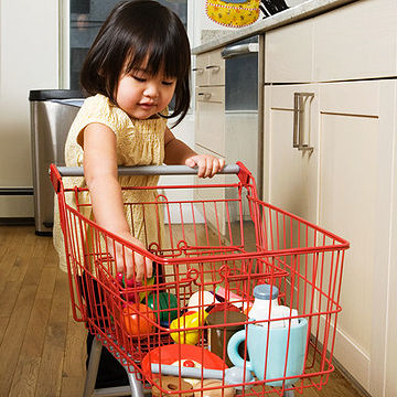 toddler pushing toy shopping cart