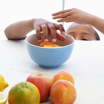 child reaching for fruit on the table