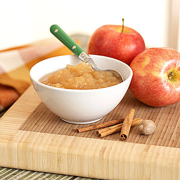 mashed apples in bowl on cutting board