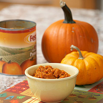 Bowl of pumpkin with pumpkins in background