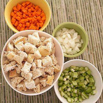 Bread cubes, celery, onions, carrots in bowls