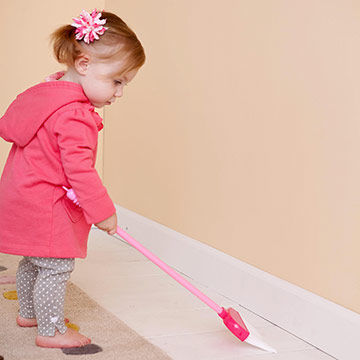 toddler sweeping floor