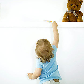 toddler reaching for toy on shelf