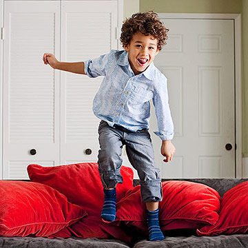 child jumping on couch