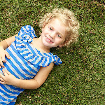 child laying in grass