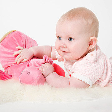baby playing with pink stuffed animal