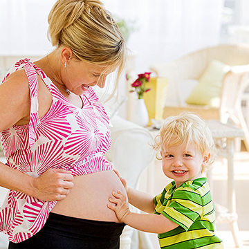 toddler touching mother pregnant belly