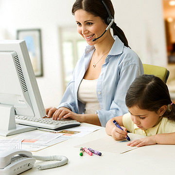 Woman in headset typing on computer with daughter