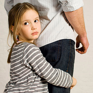 Girl clutching legs of her father