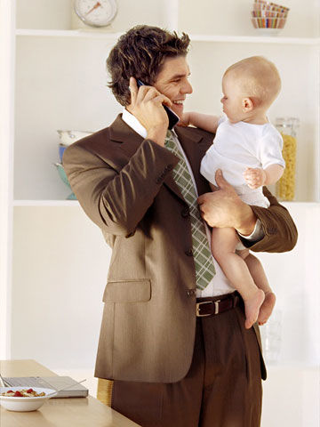 Wavy haired dad on phone, holding baby