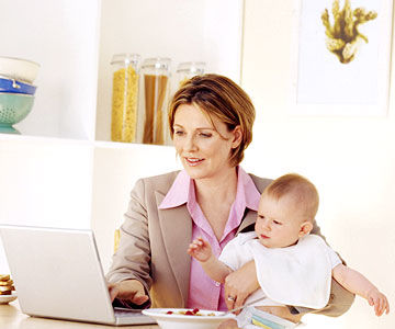 Mom on laptop holding baby