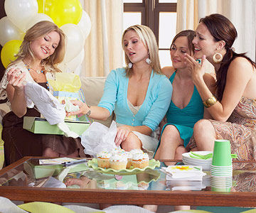 women admiring clothes at baby shower