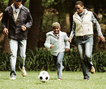 parents playing soccer with son