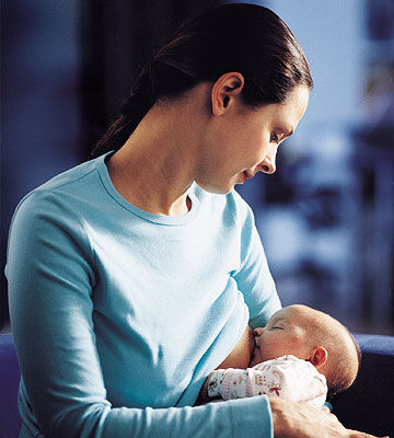 Woman in Blue Shirt Breastfeeding Baby