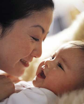 Asian Mother Snuggling Baby