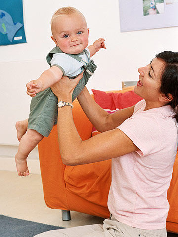 woman holding baby in air