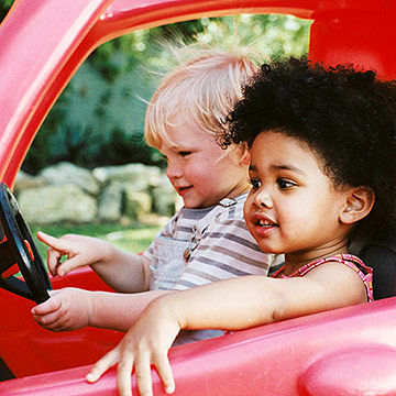 toddlers playing in red car