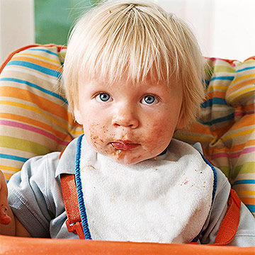 toddler in high chair with messy face