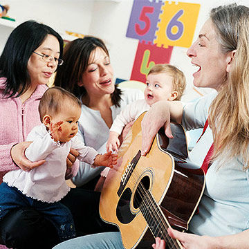 woman playing guitar to babies