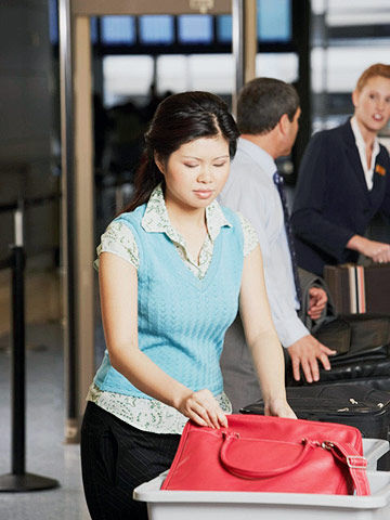 asian woman at airport going through metal detector