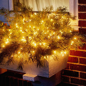 Window box with white lights and pine greenery