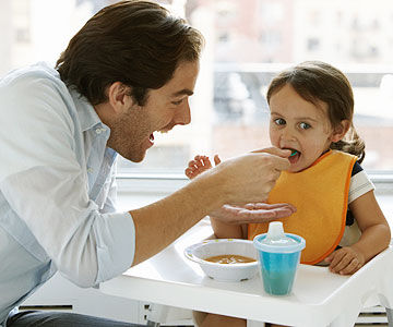 father feeding daughter in highchair